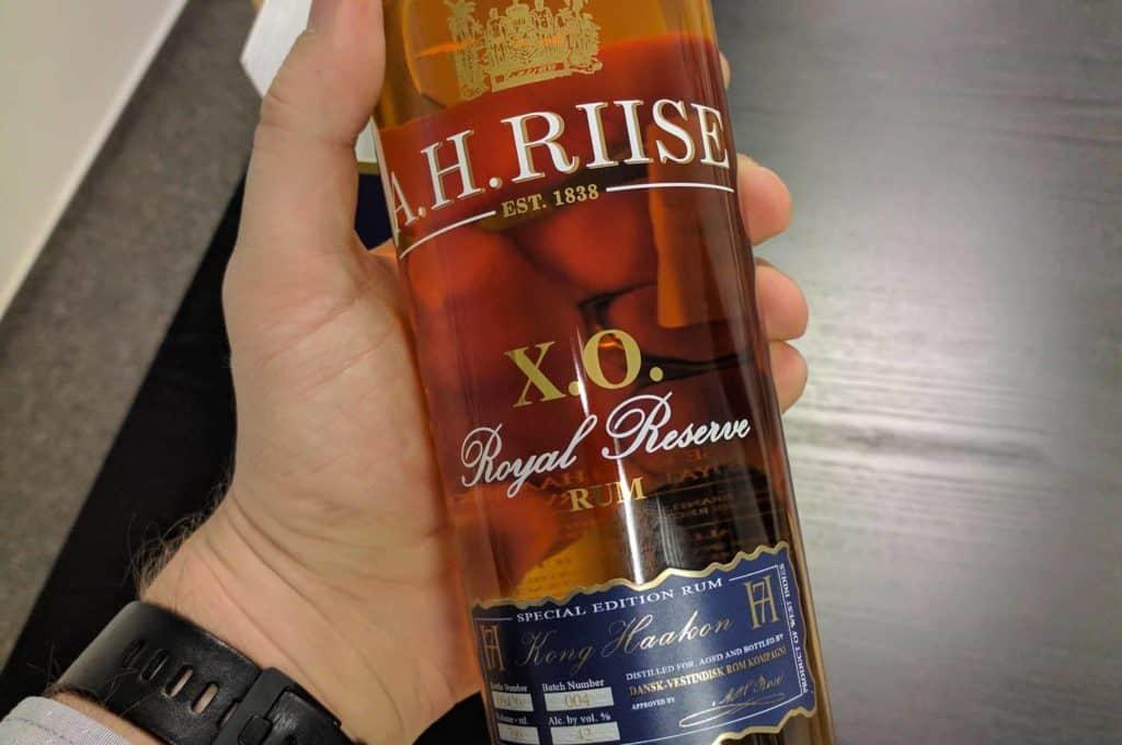 Jak vypadá láhev Kong Haakon od A. H. Riise v ruce